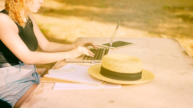 Unrecognizable female sitting at desk and working on laptop outdoors