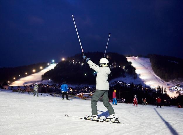 スキーストックで手を上げている認識できない女性スキーヤー。背面図。紺碧の空の下でゲレンデと樹木が茂った山