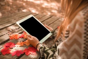 Unrecognizable female using tablet in autumn park