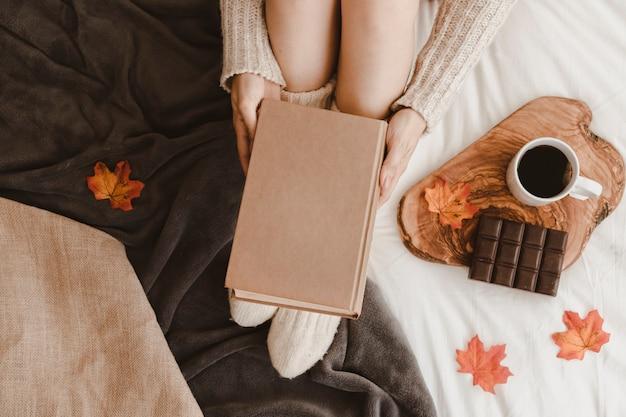 Femmina irriconoscibile con libro vicino a tè e cioccolato