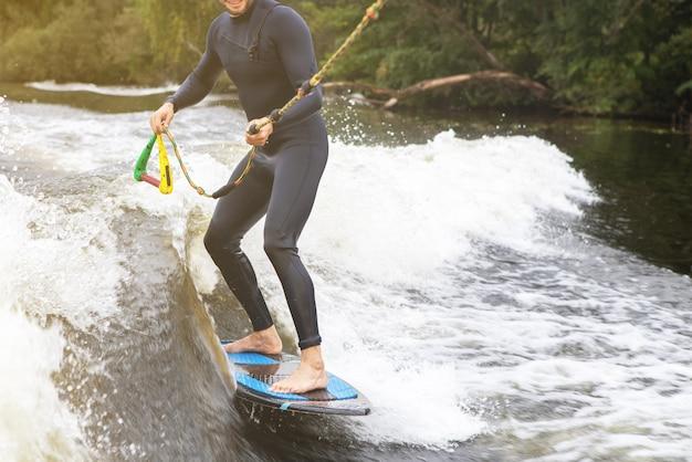 認識できないフィットの白人男性は、夕陽の中で夕方に川や湖でウェイクサーフィンに乗ります。ウォータースポーツ、休日、週末の活動のコンセプト。側面図。水平。