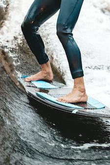 До неузнаваемости подтянутый кавказский мужчина катается на вейсерфинге на реке или озере вечером на заходящем солнце. концепция водных видов спорта, мероприятий на выходных. передний план. тонированное, контрастное изображение. стиль жизни. вертикальный.
