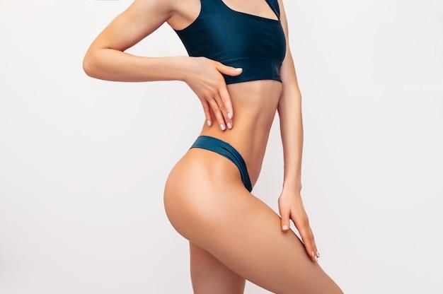 Непознаваемая подходящая женщина в черном женское бельё на белой изолированной стене. мускулистая стройная привлекательная самка с плоским животом. скопируйте место для текста. уход за телом, здоровая и спортивная жизнь, концепция удаления волос