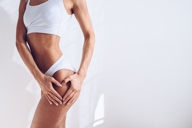 Непознаваемая подходящая женщина в белом женское бельё на белой изолированной стене. мускулистая стройная привлекательная самка с плоским животом. скопируйте место для текста. уход за телом, здоровая и спортивная жизнь, концепция удаления волос