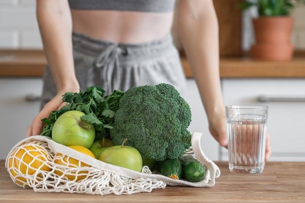 Неузнаваемая фитнес-девушка с сетчатой сумкой, полной здоровых овощей и фруктов на фоне современной кухни