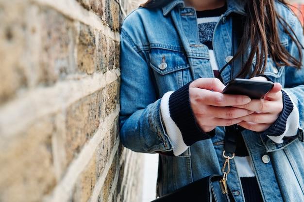通りの壁に対して彼女の電話をチェックしている認識できない女の子。スペースをコピーします。