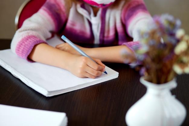 認識できない女の子の宿題、教育の概念、コロナウイルスの自宅学校検疫を書きます。家庭教師。
