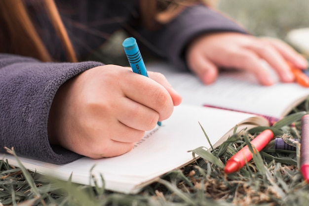 Unrecognizable girl doodling in notebook