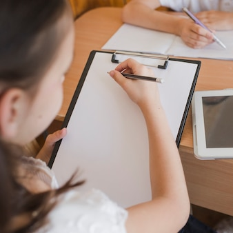 Unrecognizable girl drawing on clipboard