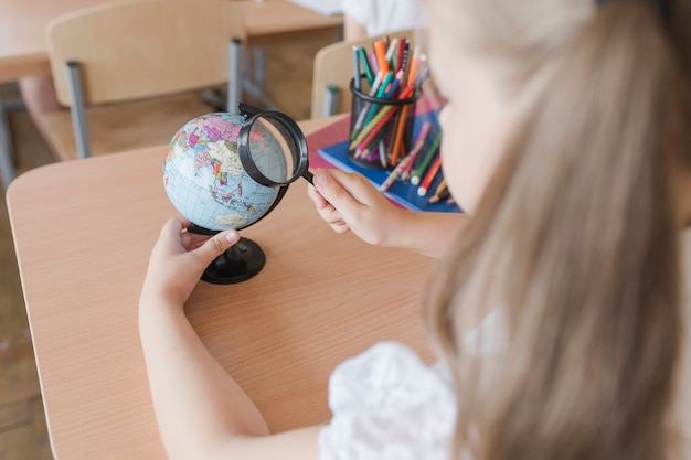 Unrecognizable girl examining globe