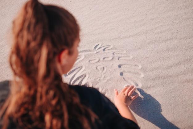 여름에 해변에서 모래에 그림을 만드는 인식 할 수없는 소녀