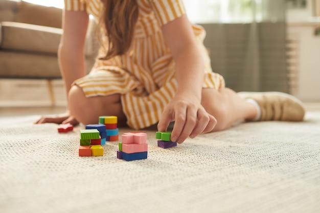 아늑한 집 인테리어에 바닥에 앉아있는 동안 화려한 블록을 가지고 노는 인식 할 수없는 소녀