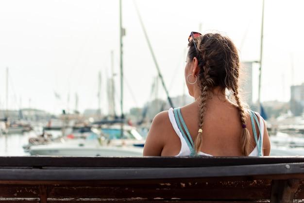항구가 내려다보이는 벤치에 앉아 있는 알아볼 수 없는 소녀