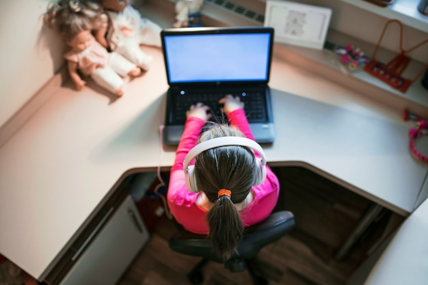 Unrecognizable girl using laptop at desk
