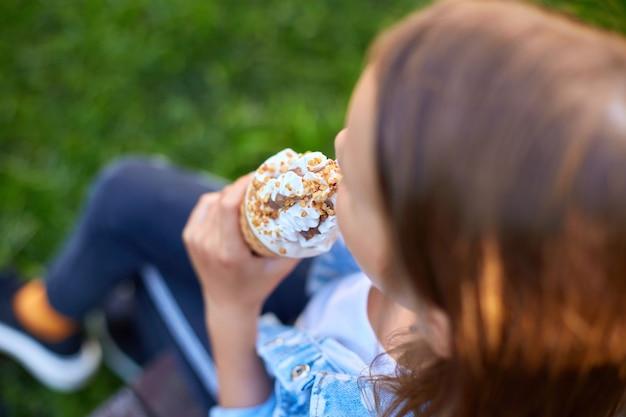 Неузнаваемая девушка с рожком мороженого в руке, отдыхающая в парке в летний день, ребенок, наслаждающийся мороженым на открытом воздухе, счастливые каникулы, лето