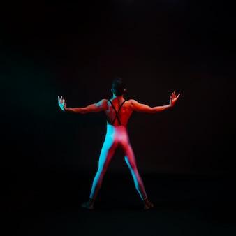 뒤에서 펼쳐지는 팔을 가진 레오타드에서 인식 할 수없는 우아한 댄서