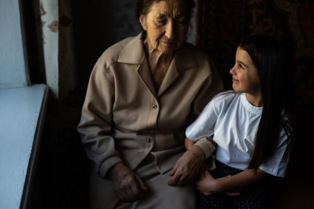 認識できない祖母と彼女の孫娘が手をつないでいます。