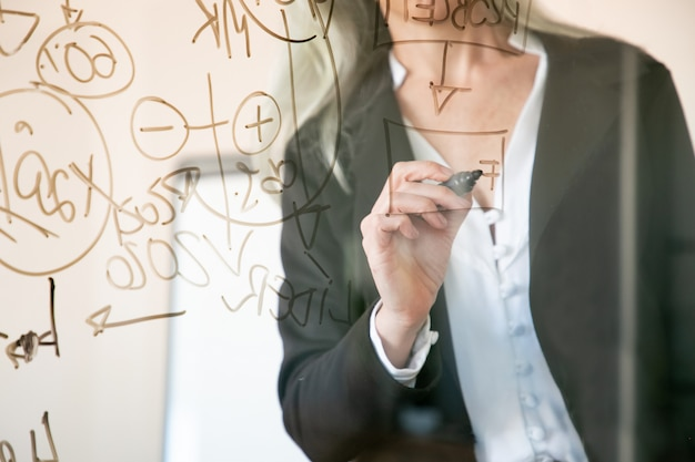 Unrecognizable grey-haired businesswoman writing on glass board. hand holding black marker and making notes for project. strategy, business and management concept