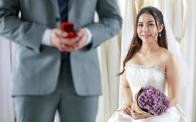 Unrecognizable groom in grey formal suit stand hold red box of diamond ring prepare giving to asian young beautiful happy bride in white wedding dress holding flower bouquet in blurred background.