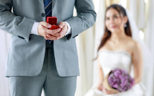 До неузнаваемости жених в сером формальном костюме держит красную коробку с бриллиантовым кольцом, готовится подарить азиатской молодой красивой счастливой невесте в белом свадебном платье, держащей букет цветов на размытом фоне.