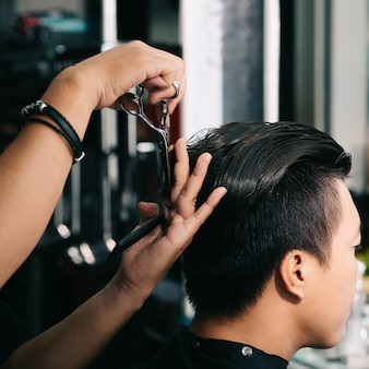 Unrecognizable hairdresser cutting asian male customer's hair with scissors in salon