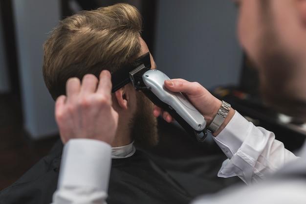 Unrecognizable hairdresser shaving hair of customer
