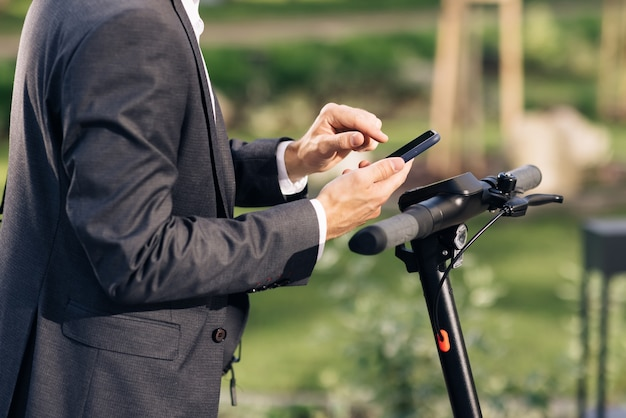 Unrecognizable hands with phone tourist taking escooter or bicycle phone application for rental