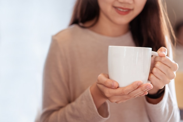 Unrecognizable happy asian woman holding a hot coffee mug in her hands