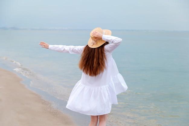 海岸で麦わら帽子を手に認識できない幸せな女性。海のビーチで日没で休む白いビーチドレスの細い脚で後ろから幸せな楽しみの女性のシルエット。