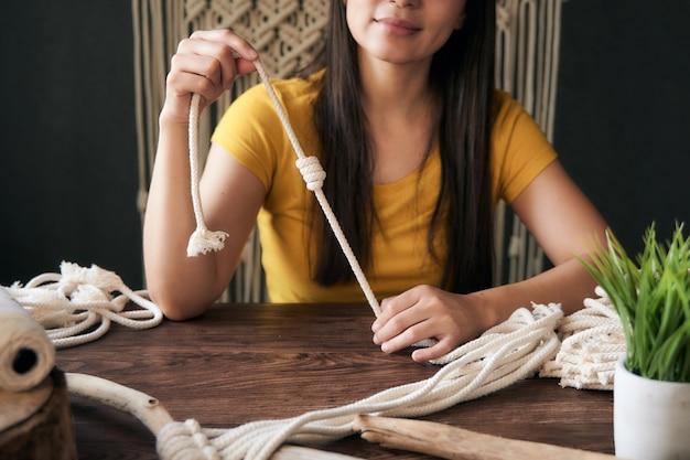 マクラメの結び目を保持している黄色の服を着た認識できない幸せな若い女性