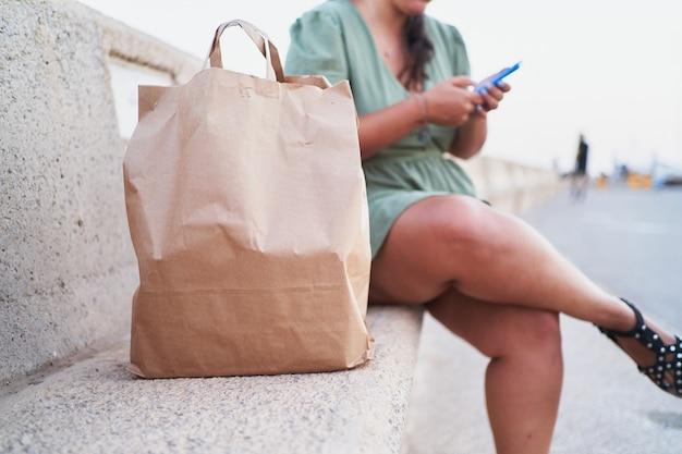 До неузнаваемости латиноамериканка сидит с телефоном рядом с сумкой для доставки