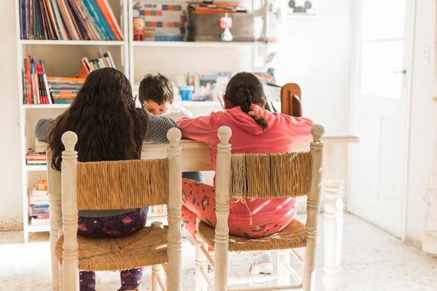 Ragazzi irriconoscibili che studiano a tavola