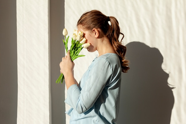 Unrecognizable lady holding white tulips