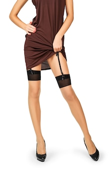 Unrecognizable lady lifting dress and showing stockings and garter