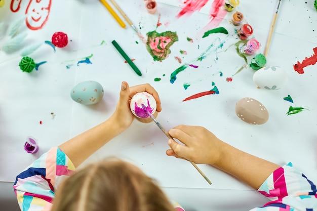 인식 할 수없는 어린 소녀 그림, 집에서 브러시 계란으로 그리기. 부활절을 준비하는 아이, 재미와 축하 잔치. 행복한 부활절, diy