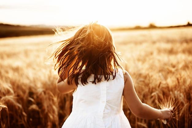 白い服を着て日没に対して麦畑で走っている認識できない少女。