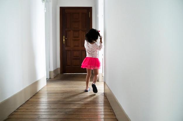 인식 할 수없는 작은 소녀는 분홍색 치마와 집 복도에서 실행. 아이들과 함께하는 가족 생활. 집에서 아이들이 재미. 실내 레저. 집 개념을 유지하십시오.