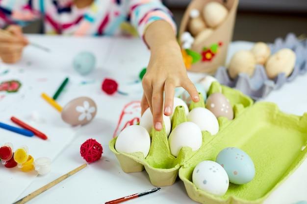 認識できない小さな女の子が家で卵を取り、絵を描き、ブラシの卵で描きます。イースターの準備をし、楽しんで、ごちそうを祝う子供。ハッピーイースター、diy