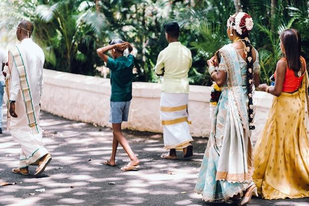 전통 의상을 입은 인식 할 수없는 현지인들이 모리셔스 사람들의 전통 웨딩 드레스 인 모리셔스 섬의 공원을 산책합니다.