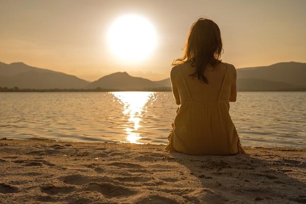 海岸の砂の上に座って、水中での光の反射とオレンジ色のセピアのビンテージ写真効果で夕日を見ている認識できない孤独な物思いにふける女性。夜明けの夢見る人