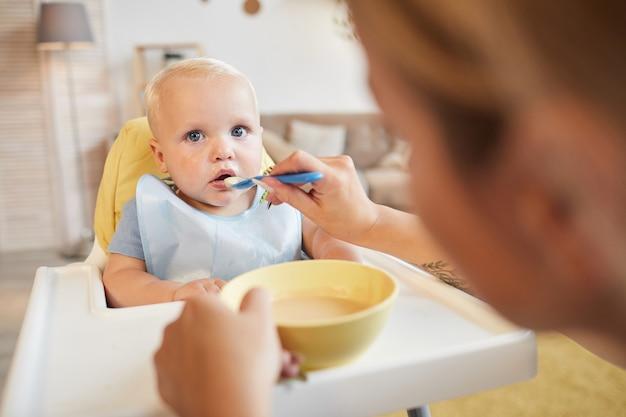 До неузнаваемости любящая мать кормит своего маленького сына вкусным фруктовым кабачком над головой