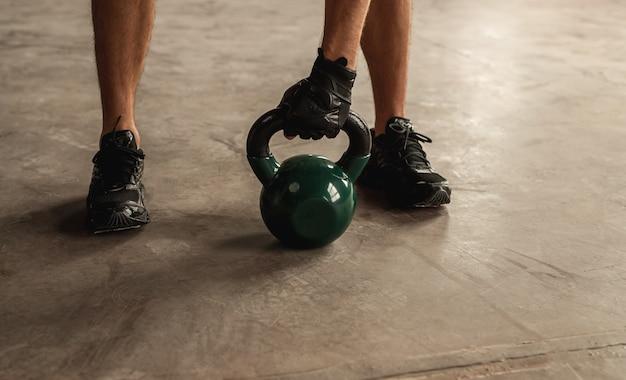 ジムでの重量挙げトレーニング中にコンクリートの床で重いケトルベルを握っている認識できない男性アスリート