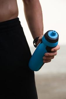 Несознаваемый мужской спортсмен, держащий пластиковую бутылку