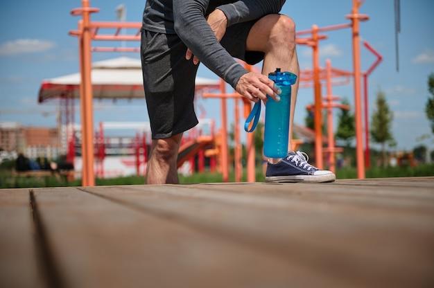 スポーツフィールドでの認識できない男性アスリートの脚、水でボトルを取っているスポーツマン、屋外でのトレーニング中に体に水分を補給します。クローズアップ、トリミングされた画像