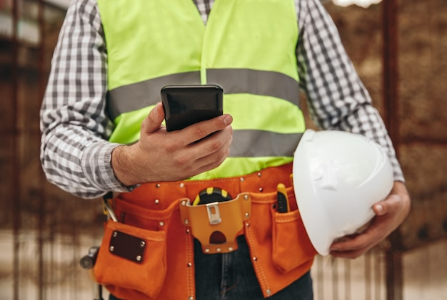 Unrecognizable male builder with helmet browsing app on smartphone during break on construction site