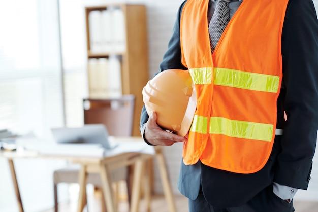 Dirigente maschio irriconoscibile del settore delle costruzioni che posa in giubbotto di sicurezza, con l'elmetto protettivo