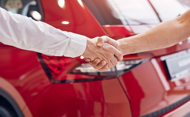 Неузнаваемый мужчина-клиент и менеджер пожимают руку красному автомобилю в современном автосалоне
