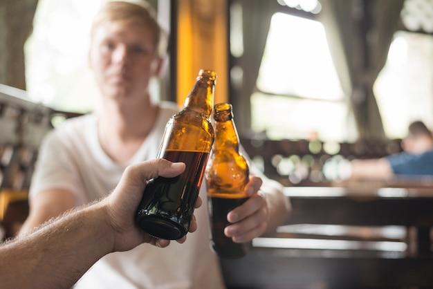 Unrecognizable male friends clinking bottles in bar