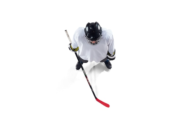 Giocatore di hockey maschio irriconoscibile con il bastone sul campo da ghiaccio e bianco