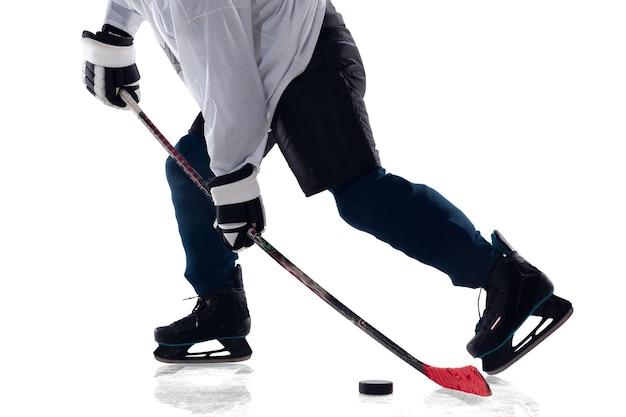 アイスコートと白い背景の上の棒を持つ認識できない男性のホッケー選手。装備とヘルメットを身に着けているスポーツマンの練習。スポーツ、健康的なライフスタイル、動き、行動の概念。閉じる。